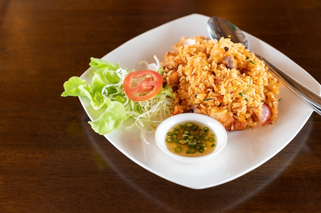 Tom yum fried rice with crispy pork on wooden table