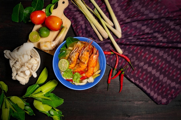 Tom yum goong spicy sour soup on wooden table and thai fabric, top view,