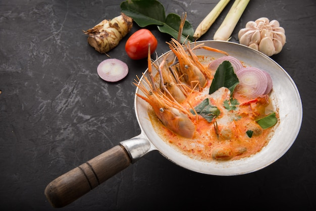 Tom yum goong spicy sour soup on wooden table top view