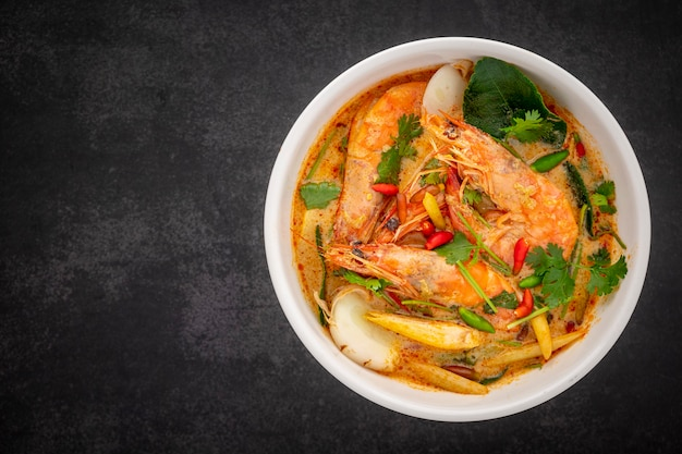 Tom yum goong, tom yum kung, thai food, hot and sour shrimp soup, creamy style in white ceramic bowl on dark tone texture background with copy space for text, top view