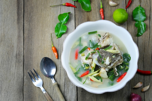 Tom yum grouper fish spicy soup of thai food in a bowl on wooden floor.