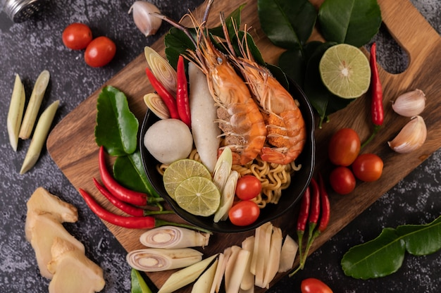 Tom yum kung in a bowl with tomato, chili, lemongrass, garlic, lemon, and kaffir lime leaves