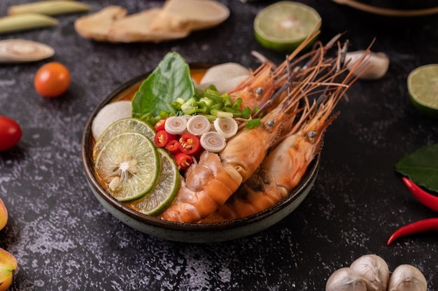 Tom yum kung in a bowl with tomato, chili, lemongrass, garlic, lemon, and kaffir lime leaves