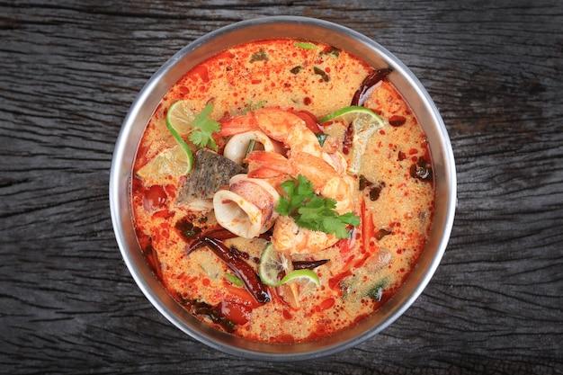 トムヤムクンまたはトムヤムクン木製テーブルトップビューのスパイシーな酸っぱいスープ