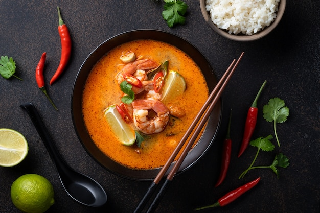 Tom yum kung spicy thai soup with shrimp in a black bowl on a dark surface, top view