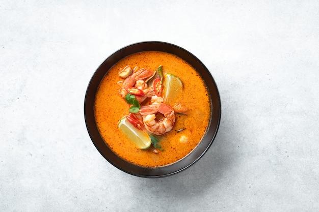 Острый тайский суп том ям кунг с креветками в черной миске на бетонном фоне, вид сверху, копия пространства