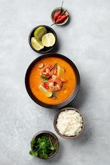 Острый тайский суп том ям кунг с креветками в черной миске на бетонном фоне, вид сверху