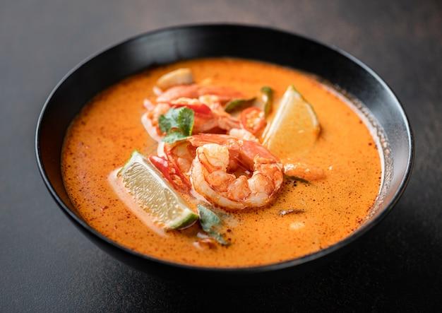 Острый тайский суп том ям кунг с креветками в черной миске на темном фоне выборочный фокус