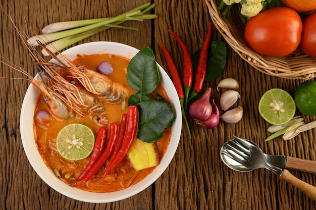 Tom yum kung thai hot spicy soup shrimp with lemon grass,lemon,galangal and chilli on wooden table, thailand food