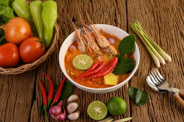 Tom yum kung тайский горячий острый суп из креветок с лимонной травой, лимоном, галангалом и чили на деревянном столе, таиландская еда