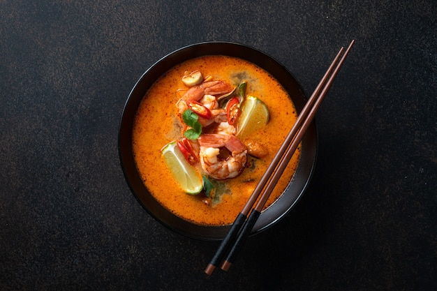 Tom yum soup with shrimp in a ceramic black bowl with chopsticks on a dark surface, top view