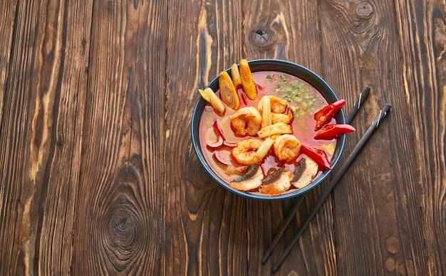 Острый суп tom yum с креветками, морепродуктами, кокосовым молоком и перцем чили в миске традиционной азиатской кухни на деревянном фоне