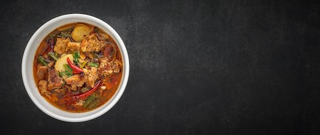 Том ям, тайская еда, острый, острый и кислый тушеный суп из говядины в миске на темно-сером столе