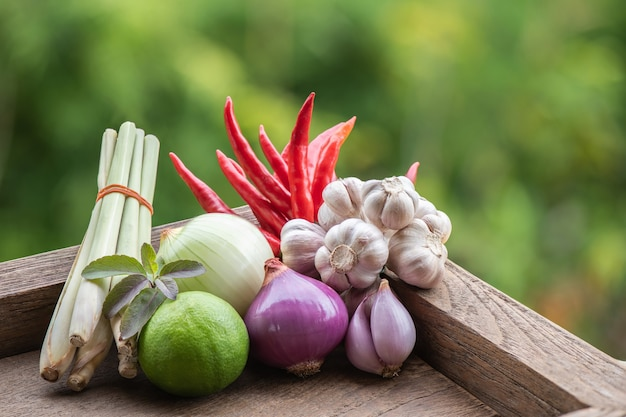 Tom yum or vegetable and herbs eat antiviral and immune to the body such as, chilli, lemongrass, lime, shallot, onion, kaempfer on nature surface. Premium Photo