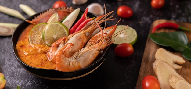 Tom yum with shrimp and crab with lime, chili, tomato, garlic, lemongrass and kaffir lime leaves.