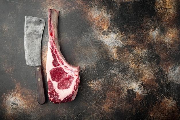 토마 호크 쇠고기 스테이크 날것과 오래된 정육점 칼