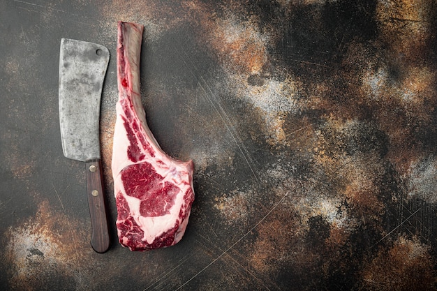 Tomahawk beef steak raw and old butcher cleaver knife