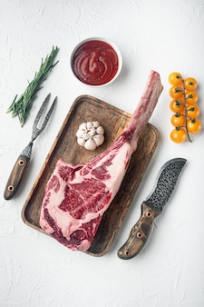 Tomahawk beef steak raw set, with seasoning and herbs, on white stone