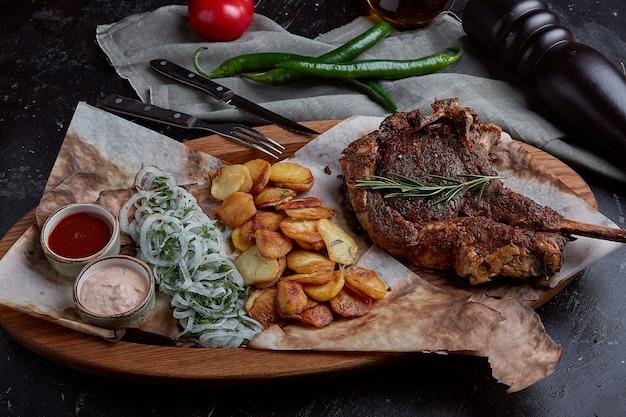 野菜とナイフをテーブルに置いたトマホークステーキ