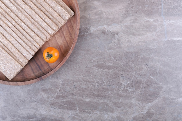 Помидор стопка хрустящих хлебцев на деревянной доске, на мраморном фоне.