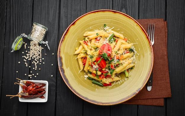 黒い木製のテーブルにトマトとベーコンのペンネパスタ