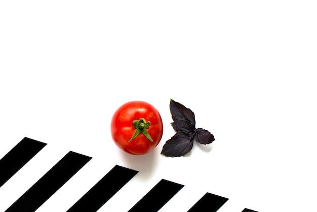黒と白の縞模様の背景にトマトとバジル。分離します。スペースをコピーします。