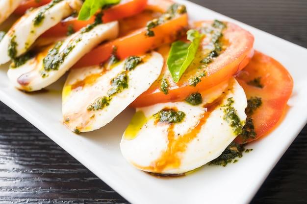 흰 접시에 토마토와 모짜렐라 치즈 샐러드