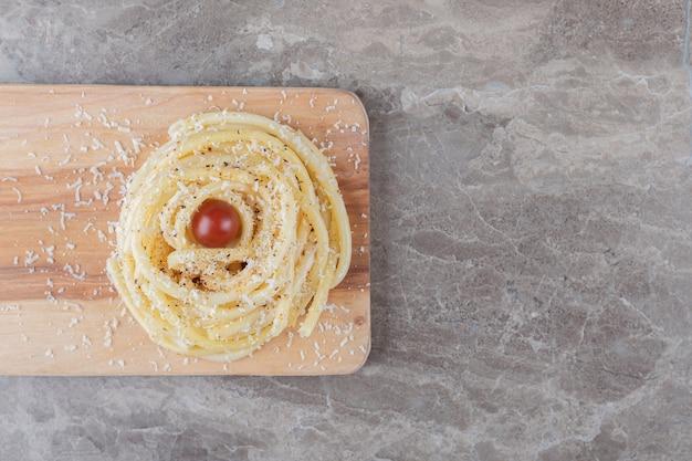 Помидоры и макароны на разделочной доске, на мраморе.