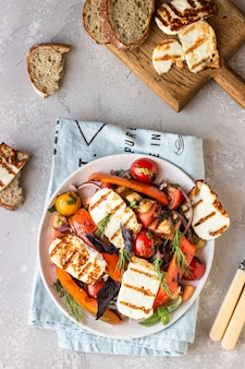 Tomato, baked pepper and onion salad with grilled cheese