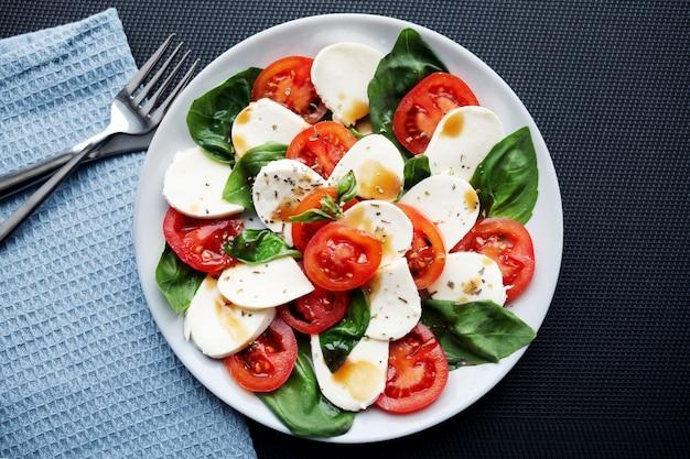 Салат из помидоров, базилика, моцареллы капрезе с бальзамическим уксусом и оливковым маслом.