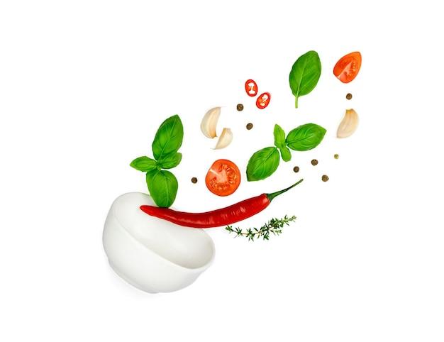 トマト、バジル、スパイス、唐辛子、にんにくのフレッシュタイムが飛んでいます。白で隔離されるビーガンダイエット食品。ボウルに落ちる、浮揚フライ。クリエイティブなコンセプト。高品質の写真