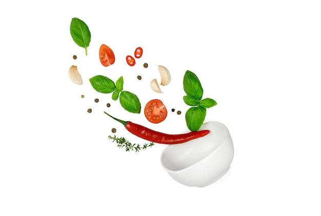 トマト、バジル、スパイス、唐辛子、にんにくのフレッシュタイムが飛んでいます。白で隔離されるビーガンダイエット食品。