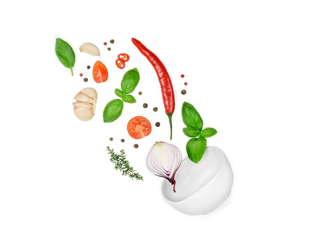 トマト、バジル、スパイス、唐辛子、にんにくのフレッシュタイム、玉ねぎが飛んでいます。白で隔離されるビーガンダイエット食品。ボウルに落ちる、浮揚フライ。クリエイティブなコンセプト。高品質の写真