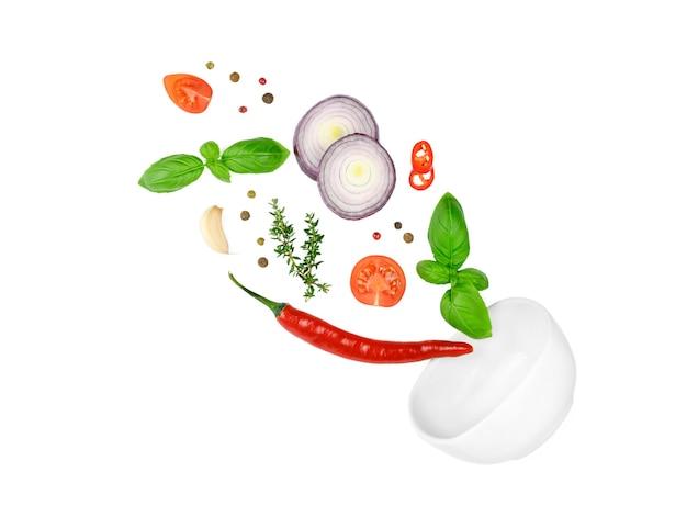 トマト、バジル、スパイス、唐辛子、にんにくのフレッシュタイム、玉ねぎが飛んでいます。白で隔離されるビーガンダイエット食品。