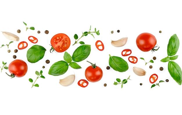 トマト、バジル、スパイス、唐辛子、玉ねぎ、にんにく。ビーガンダイエット食品、白で隔離の創造的な構成。新鮮なバジル、ハーブ、トマトのパターンレイアウト、料理のコンセプト、上面図。バナー。