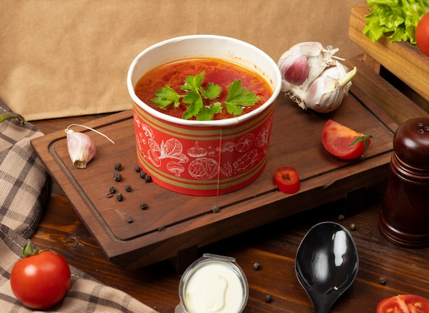 Tomato, borsh vegetable soup in disposable cup bowl served with green vegetables.