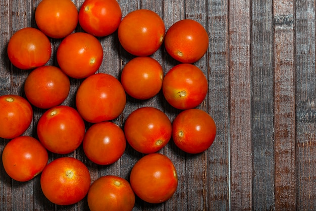Tomato cherry isolated on wooden background. top view.