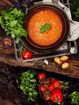 Tomato cream soup in the earthen bowl on the wooden table.
