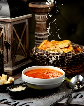 Tomato cream soup with grated cheese and crackers