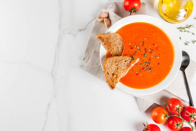 Tomato cream soup with olive oil and herbs, with toasted bread, on white marble ,  copyspace top view