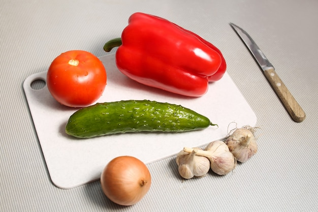 토마토, 오이, 후추, 양파, 마늘 세트 샐러드. 당신의 식단과 건강한 식습관을위한 신선하고 건강한 식사. 체중 감량을위한 간식, 저녁 식사, 점심 식사, 아침 식사.