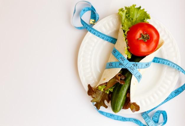 トマト、キュウリ、サラダは皿の上に住んでいます、白い背景のピタパンに巻尺を巻いた青い、減量と適切なフィットのライフスタイル、ダイエットのコンセプト、コピースペース