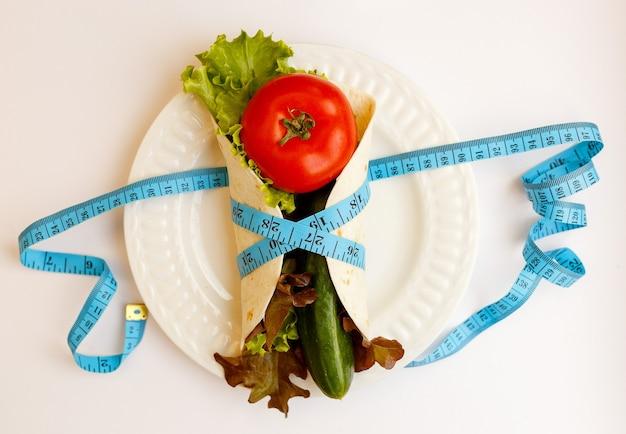 トマト、キュウリ、サラダは皿の上に住んでいます、白い背景のピタパンに巻尺を巻いた青い、減量と適切なフィットのライフスタイル、ダイエットのコンセプト