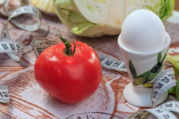 テーブルの上のトマト、卵、キャベツと定規。自然食品