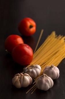 Tomato, garlic and raw spaghetti on wood.