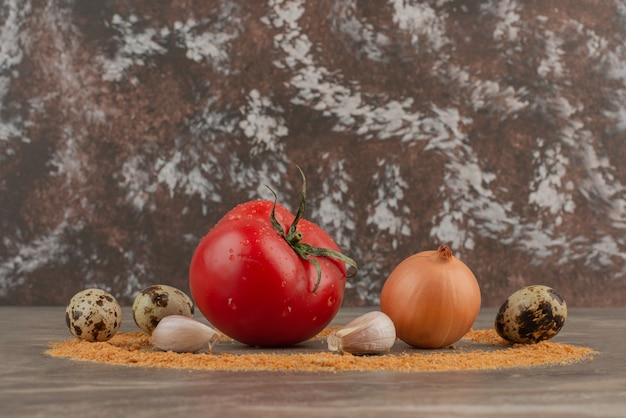 Помидор, чеснок, лук, крошки и перепелиные яйца на мраморном фоне.