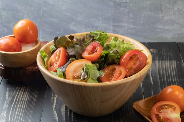 Tomato and green oak lettuce salad on bowl