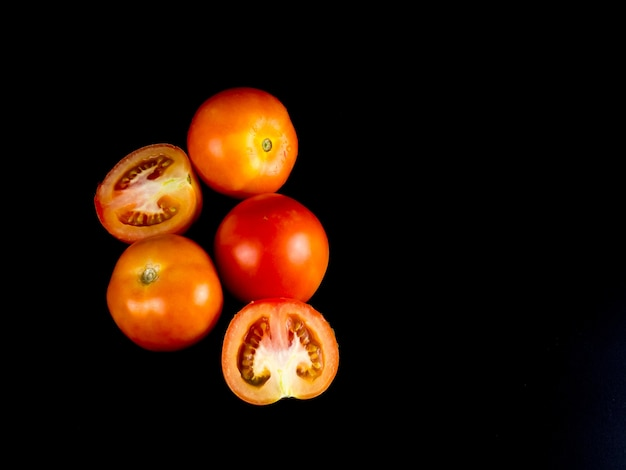 Tomato and half on black background