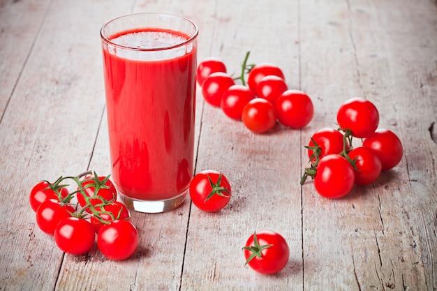Томатный сок в стеклянных и свежих помидорах