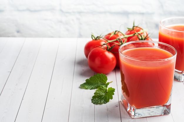 Томатный сок в стеклянных очках и свежие спелые помидоры на ветке.